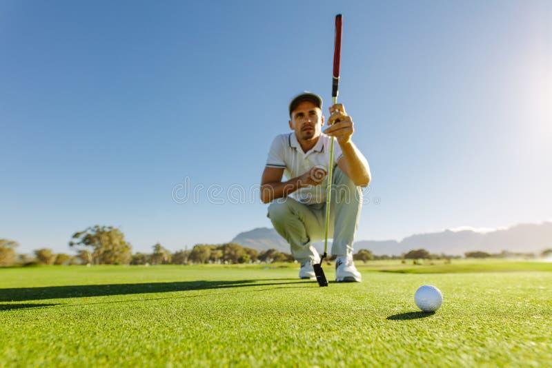 Golfspelerstudie green alvorens schot te zetten royalty-vrije stock afbeelding