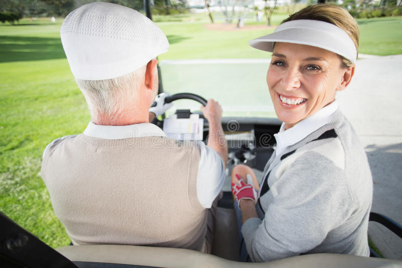 Golfspelpar som kör i deras golfbarnvagn med kvinnan som ler på kameran royaltyfria foton
