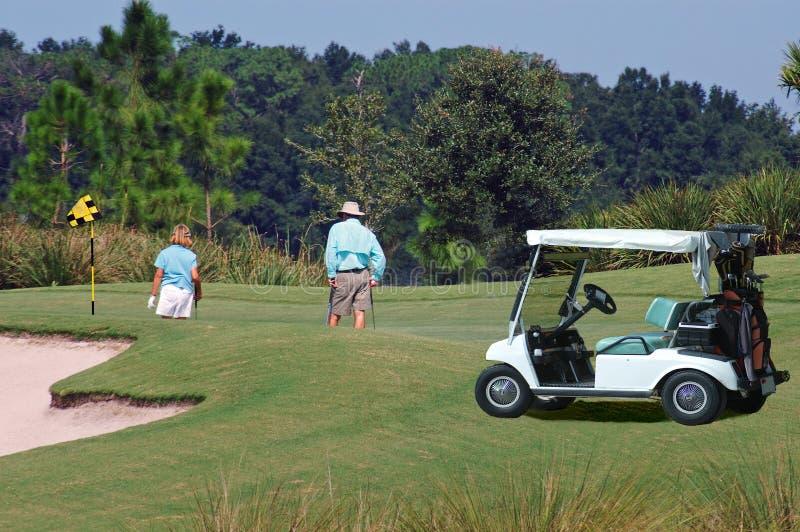 Golfspieler auf Grün mit Wagen stockfotografie