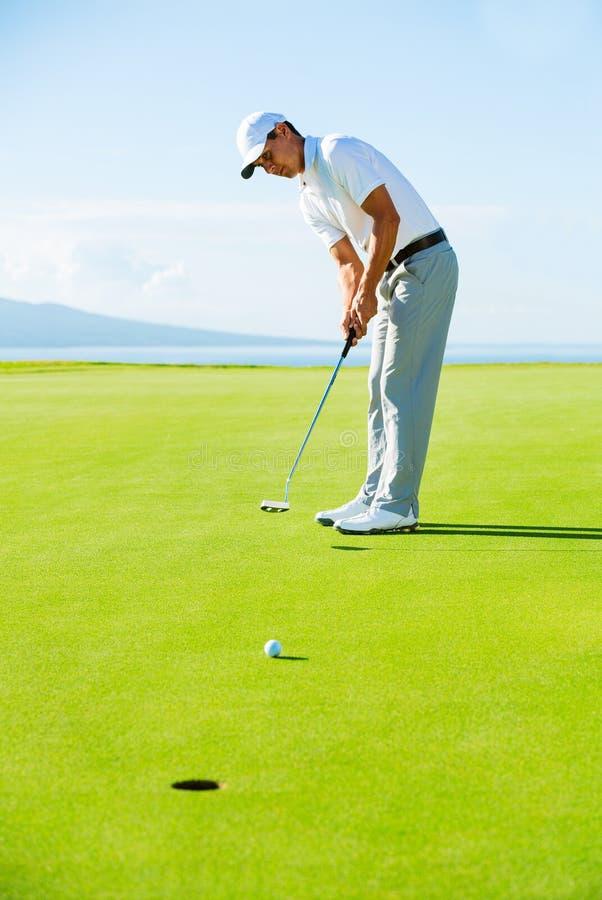 Golfspieler auf setzendem Grün lizenzfreie stockfotografie