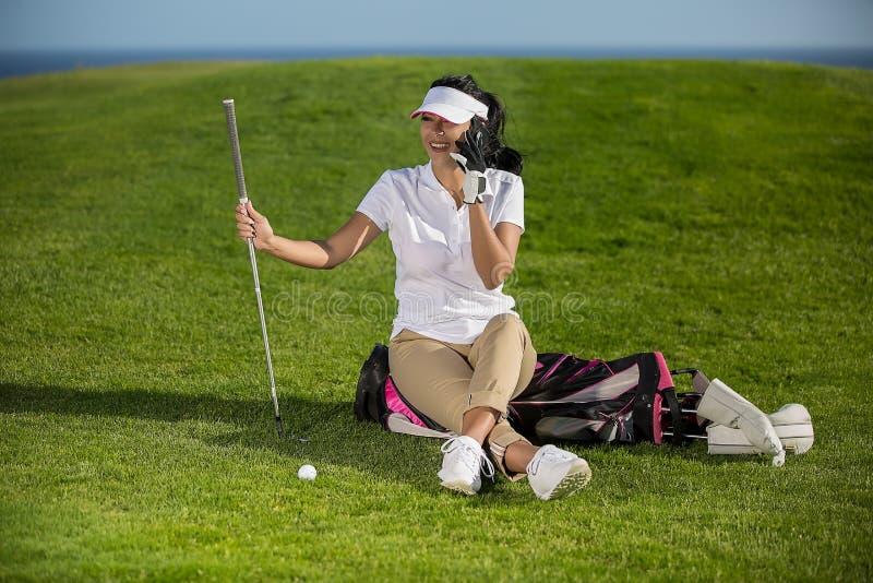 Golfspieler, der über Telefon auf Feld plaudert lizenzfreies stockbild