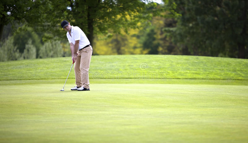Golfspieler, der auf Grün sich setzt stockfotos