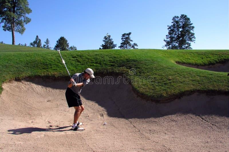 Golfspieler, der aus einem Sandfang heraus schlägt lizenzfreies stockbild