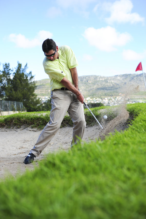 Golfspieler, der aus einem Sandfang heraus spielt lizenzfreie stockfotografie