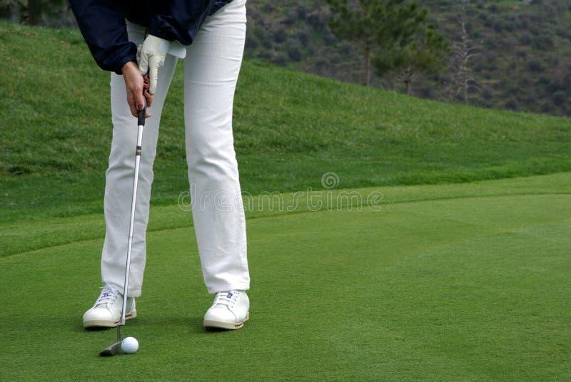 Golfspieler, der die Kugel setzt stockfotografie
