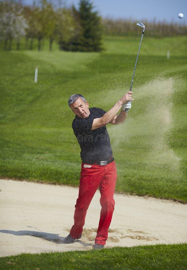 Golfspieler, der eine Kugel im Bunker schlägt stockfoto