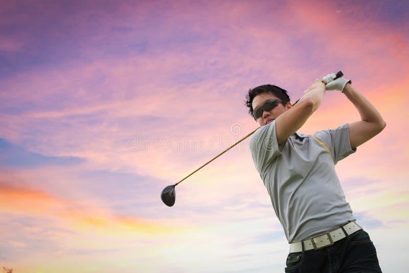 Golfspieler, der einen Golfball schießt lizenzfreies stockfoto