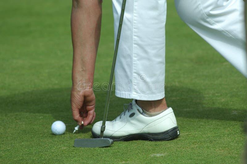 Golfspieler, der Golfball auf ein T-Stück platziert stockfoto
