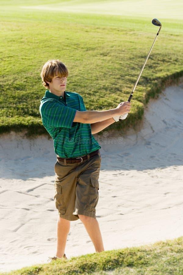 Golfspieler, der Golfball aus einem Sandfang heraus schlägt stockbild