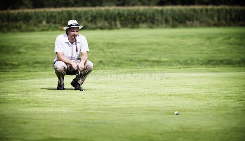 Golfspieler, der Grün bevor dem Setzen analysiert. stockbilder