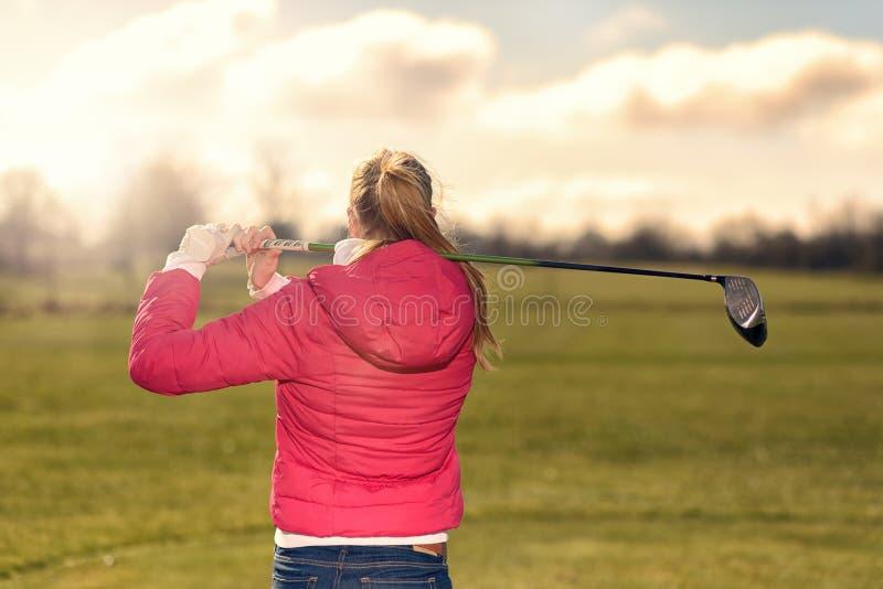 Golfspieler, der ihren Antrieb vom T-Stück aufpasst lizenzfreies stockfoto