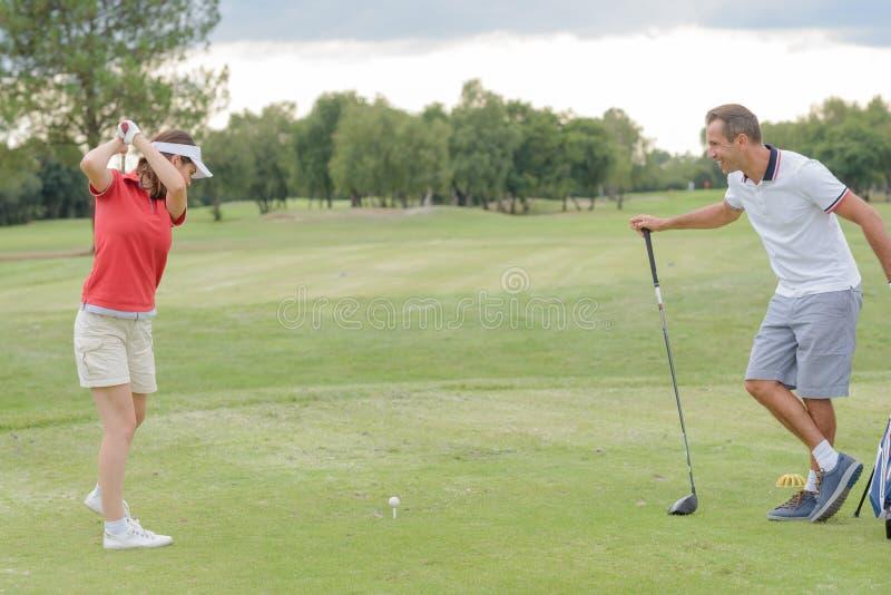 Golfspieler, der versucht, Ball zu schlagen stockfotos