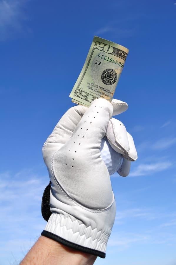 Golfspieler, der ZwanzigDollarschein anhält lizenzfreies stockbild