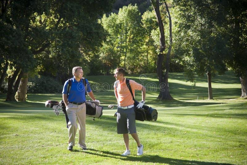 Golfspieler, die auf dem Kurs sprechen stockfoto