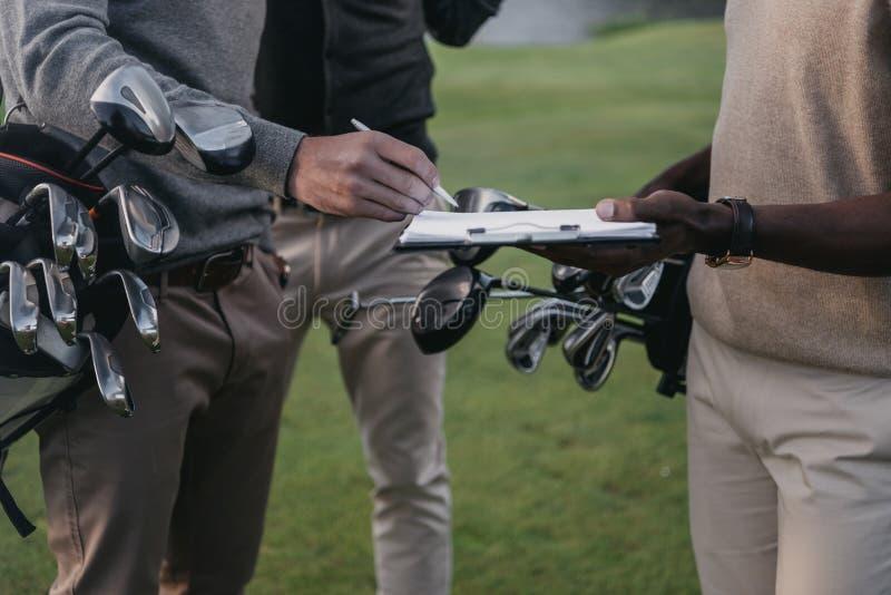 Golfspieler, die Vereine in den Taschen halten und Papiere auf Klemmbrett unterzeichnen lizenzfreie stockfotografie