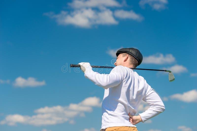 Golfspieler mit einem Golfclub reibt eine Krankrückseite stockfotografie