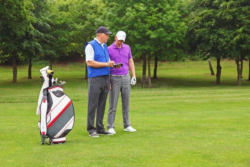 Golfspieler und Transportgestell, die einen Kursführer betrachten stockfotos