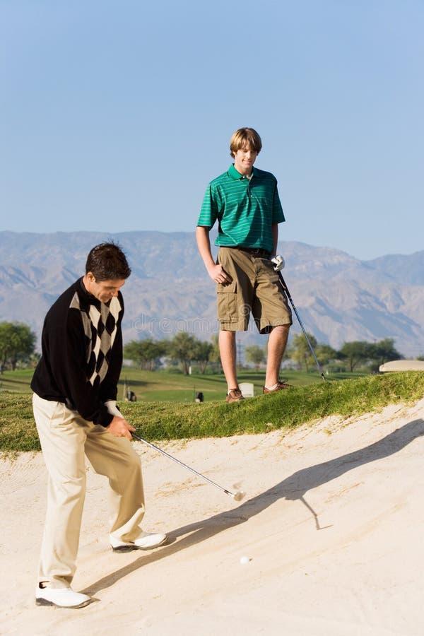 Golfspieler ungefähr, zum des Balls aus einem Sand-Bunker heraus zu schlagen lizenzfreies stockbild