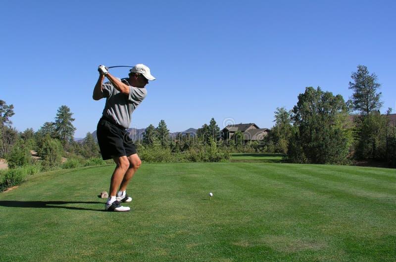 Golfspieler ungefähr, zum des Golfballs des T-Stücks weg anzutreiben stockfotografie
