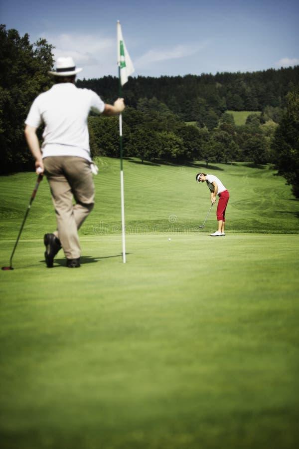 Golfspieler zwei auf Grün lizenzfreie stockbilder