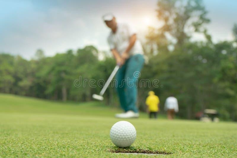 Golfspieleraktion, zu gewinnen, nachdem lang Golfball auf das grüne Golf gesetzt worden ist stockfoto