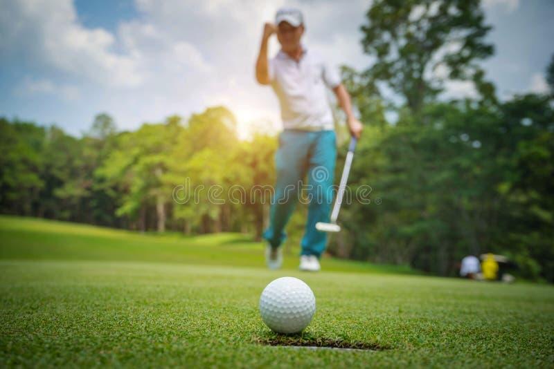 Golfspieleraktion, zu gewinnen, nachdem lang Golfball auf das gr?ne Golf gesetzt worden ist stockbilder