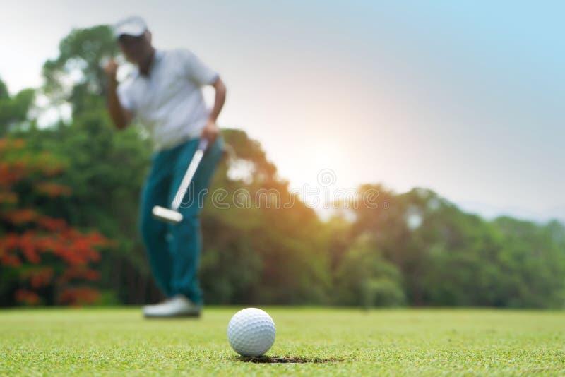 Golfspieleraktion, zu gewinnen, nachdem lang Golfball auf das gr?ne Golf gesetzt worden ist stockfotografie