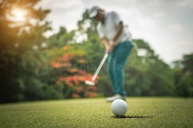 Golfspieleraktion, zu gewinnen, nachdem lang Golfball auf das gr?ne Golf gesetzt worden ist lizenzfreie stockbilder