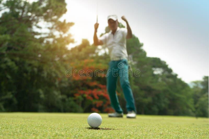 Golfspieleraktion, zu gewinnen, nachdem lang Golfball auf das gr?ne Golf gesetzt worden ist stockfotos