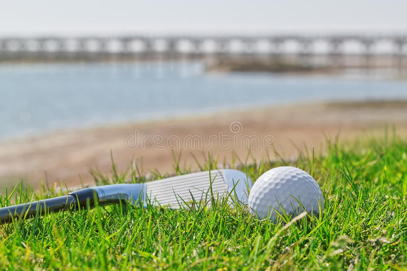 Golfstok en bal op gras met een achtergrond van aard. stock afbeeldingen