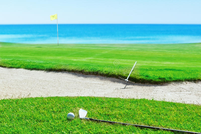 Golfstok en bal op gras tegen het overzees. Hark dichtbij het zand royalty-vrije stock foto