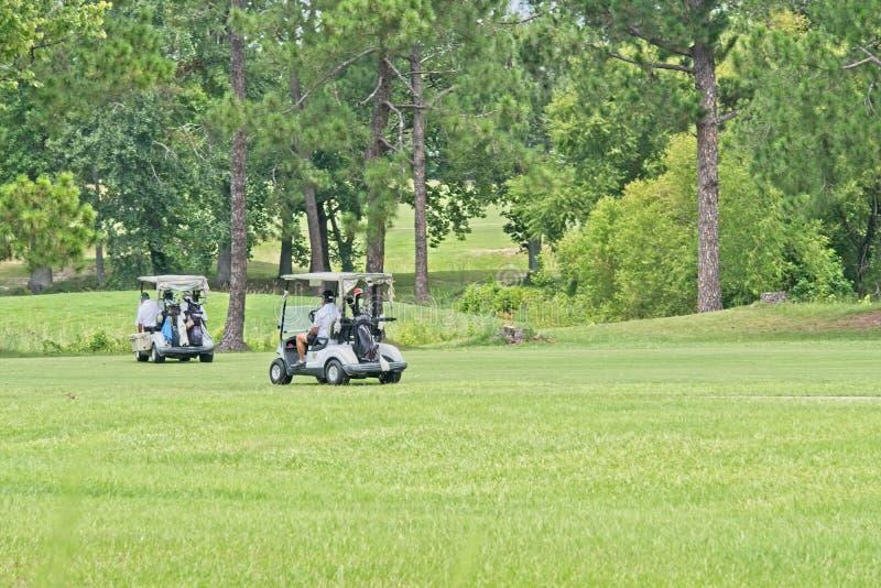 Golfvagnar på en grön golfbana arkivbild