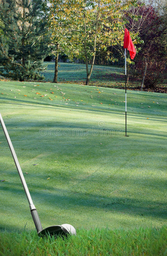 Golpe de la pelota de golf sobre verde con el club imagenes de archivo