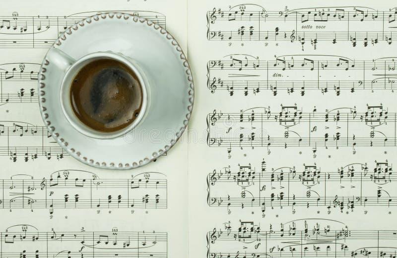 Golpe del café sólo en la taza y el platillo blancos en notas clásicas impresas de la música como fondo Tiempo de la pausa imagen de archivo libre de regalías