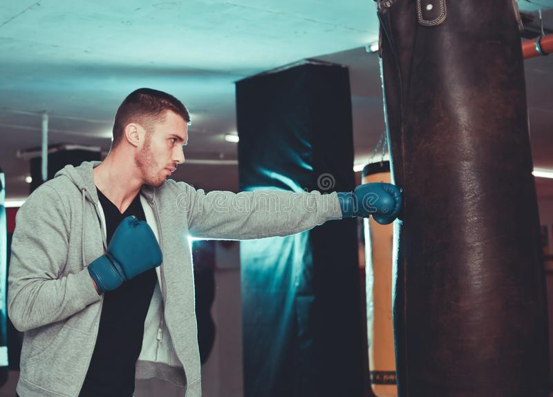 Golpe directo concentrado del boxeador con el saco de arena fotos de archivo