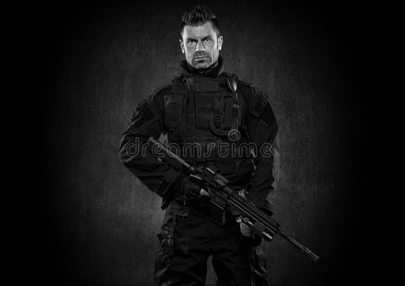 GOLPE do agente da polícia dos ops das especs. no estúdio uniforme preto foto de stock