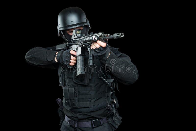 GOLPE do agente da polícia dos ops das especs. no estúdio uniforme preto imagens de stock