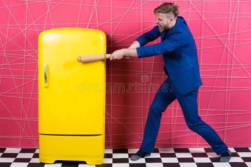 Golpe elegante formal del traje del hombre con el refrigerador retro del amarillo del vintage del palo de madera El soltero hambr foto de archivo