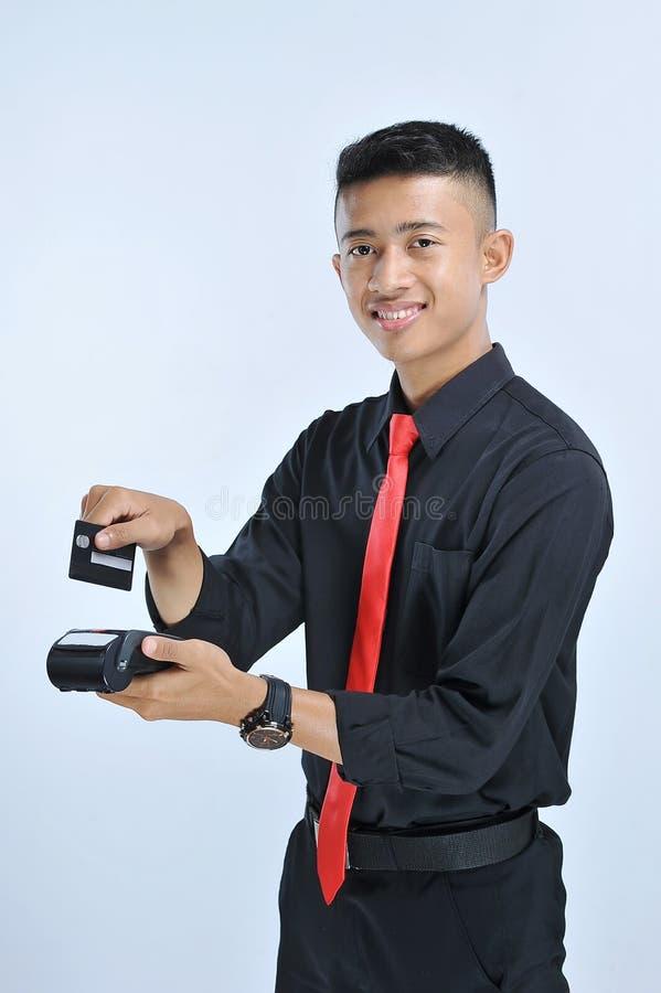 Golpe fuerte feliz del hombre asiático joven del negocio una tarjeta de crédito/una tarjeta de débito fotos de archivo