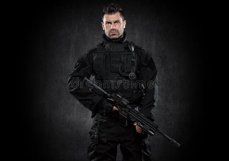 GOLPE VIOLENTO del oficial de policía de los ops de espec. en estudio del uniforme del negro imagen de archivo