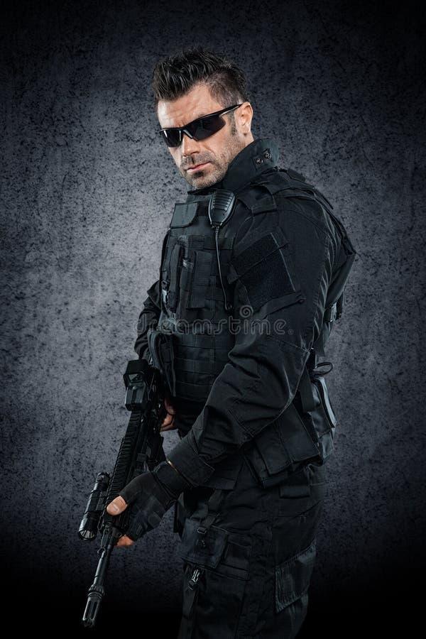 GOLPE VIOLENTO del oficial de policía de los ops de espec. en estudio del uniforme del negro fotografía de archivo