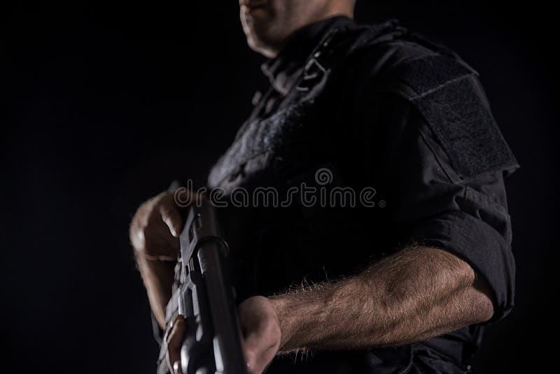GOLPE VIOLENTO del oficial de policía de los ops de espec. en uniforme del negro fotografía de archivo
