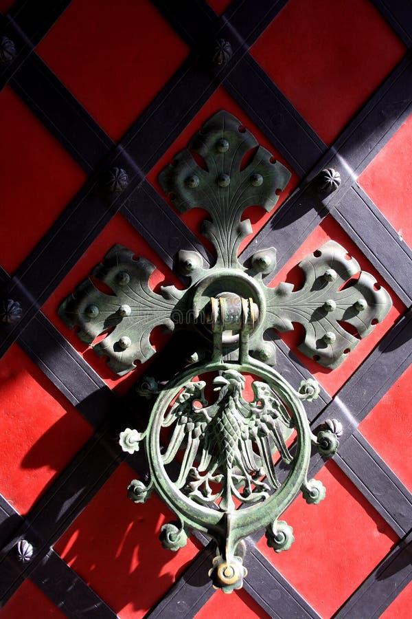 golpeador de puerta del Hierro-molde con el águila en la puerta roja imagenes de archivo