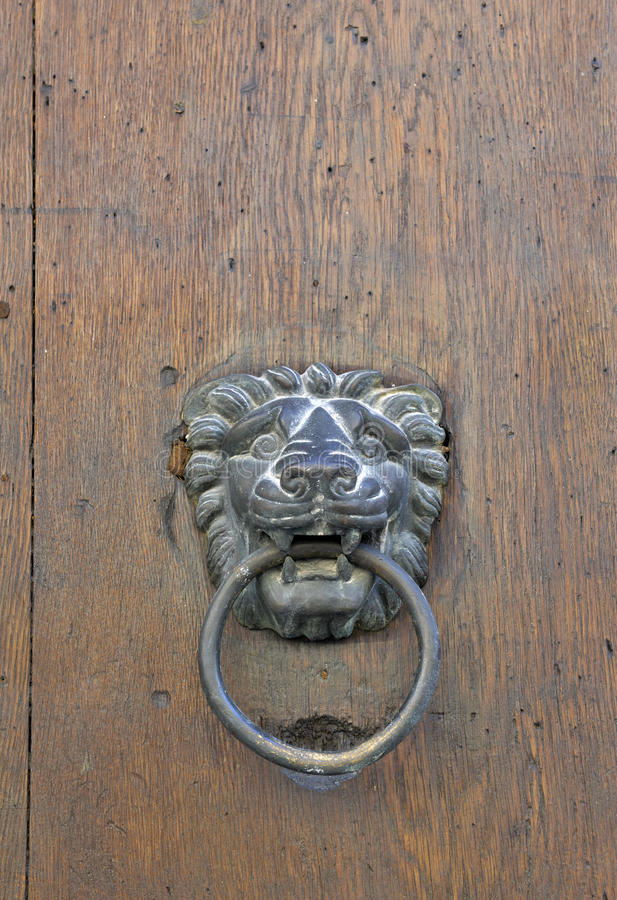 Golpeador de puerta del león en puerta de madera vieja imagenes de archivo
