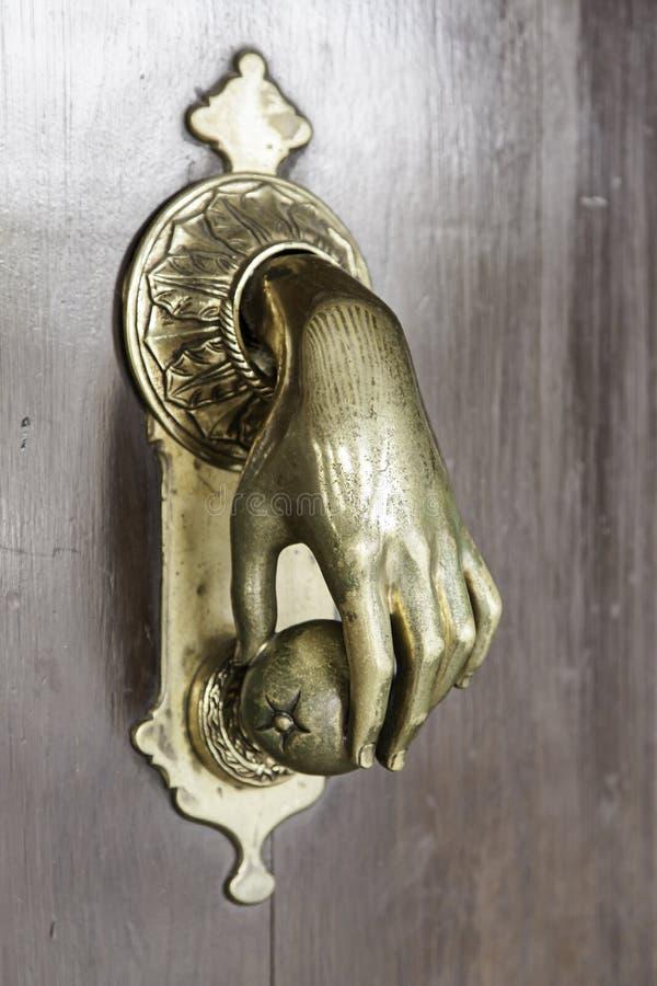 Golpeador de puerta en la forma de la mano foto de archivo