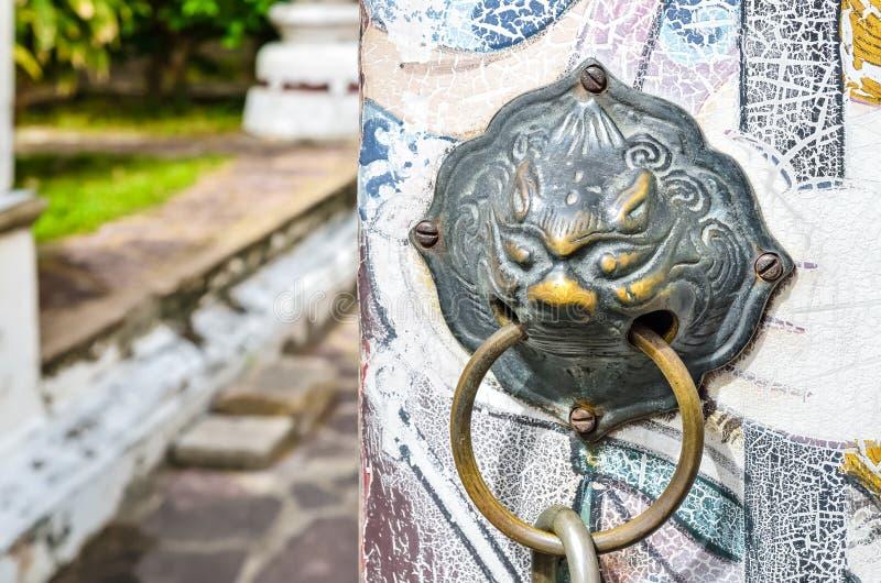 Golpeador de puerta principal del león en puerta de madera vieja imagenes de archivo