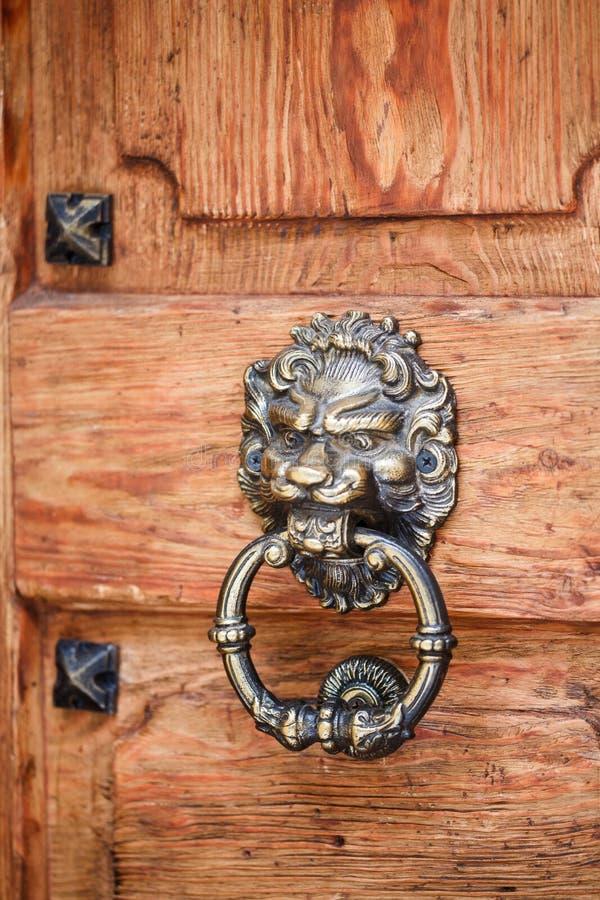 Golpeador principal del león en una puerta de madera vieja Puerta del vintage imágenes de archivo libres de regalías
