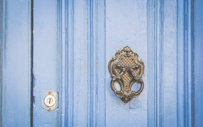 Golpeador viejo del metal en puerta de madera azul imagen de archivo libre de regalías