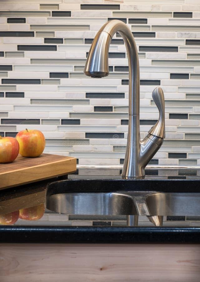 Golpecito corriente en fregadero y grifo modernos de cocina foto de archivo libre de regalías