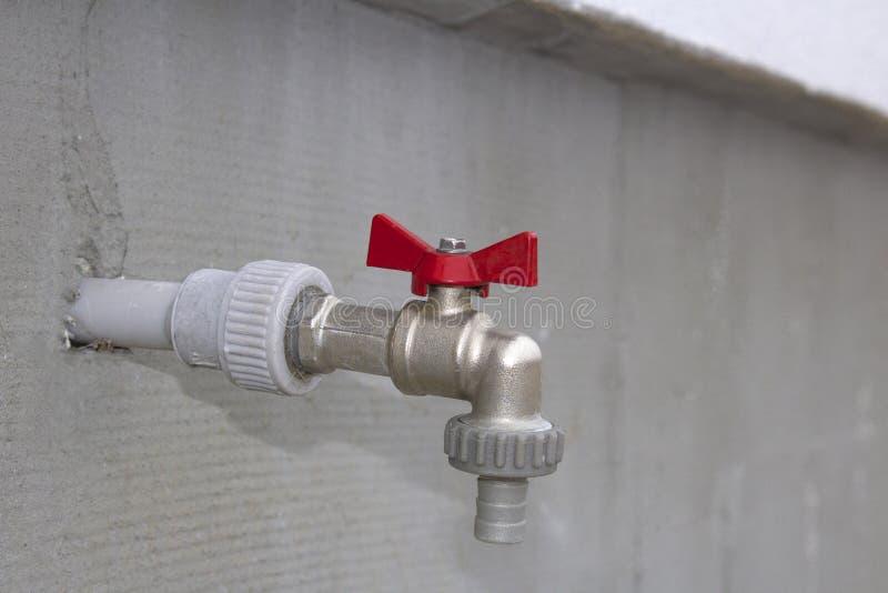Golpecito de agua cerrado en la pared al aire libre imagen de archivo